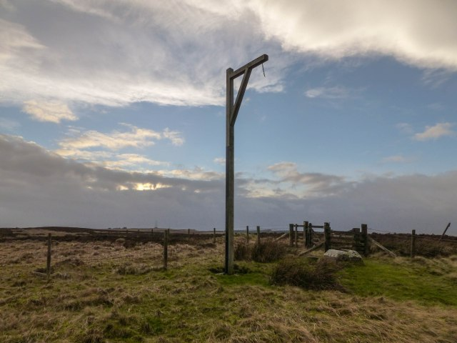 Winter's Gibbet with the stone cross base (Steng Cross) to its right.